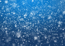 Falling snow on the blue background Royalty Free Stock Photos