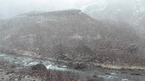 Falling snow in a valley stock video footage