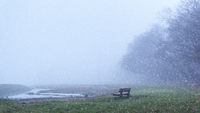 Falling Snow. View of bench in field with falling snow royalty free stock photography
