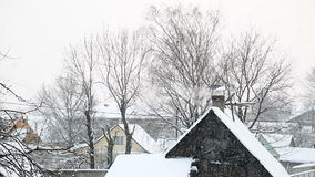 The falling snow in the village of bath house. Falling snow in the village of bath house from the chimney smoke stock video