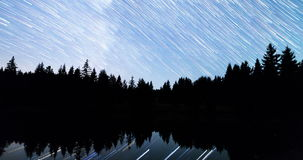 Falling stars Comet mode Lake 4k tilt. A view of the stars of the Milky Way with a silhouette of a pine trees forest near a lake in the mountain. Comet mode stock footage