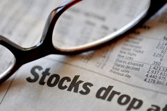 Falling Stock Market. Business section of a newspaper and glasses.  Stagflation and falling stocks Stock Photo