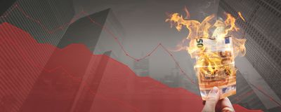 Falling stock prices – burning 50€ banknote in front of a declining graph. Burning 50 Euro banknote held by a hand. The background shows a declining stock illustration