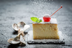 Falling sugar powder on cheesecake with cherry Stock Photography