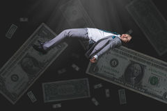 Falling and uncouncious businessman in formal wear with bank note Stock Photo