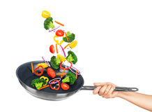 Falling vegetables in frying pan Stock Photography