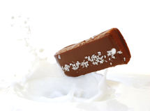 Falling wafer to the milks. Falling brown wafer to the white milks on white background Stock Photography