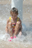 Falling Water. Little girl sitting on the ground under a water fountain at a water park. The water is in motion and splashes around her Stock Image