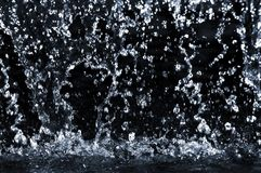 Falling water. Drops on dark background close up Royalty Free Stock Photos