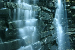 Falling water cascade and rocks. Closeup of Falling water cascade over rocks Royalty Free Stock Photos
