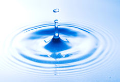 Falling water drop close up in blue. Stock Photo