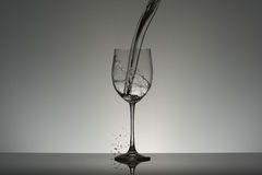 Falling water flow into a wineglass. Falling water flow into a big size wineglass on gray background Royalty Free Stock Photography