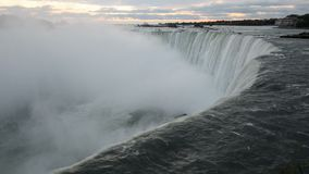 The falling water of Niagara Falls in the early morning pulls into the depth