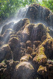 Falling water. Water falling off the rock cliff in the forest Royalty Free Stock Photo