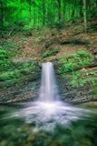 Falling water from the rock in the green forest, vertical image suitable for wallpaper. Lumshory, Carpathians royalty free stock images