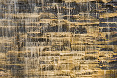 Falling water stream against stonework rough texture Royalty Free Stock Image
