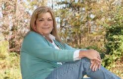 fallladyen poserar utomhus sitter Fotografering för Bildbyråer