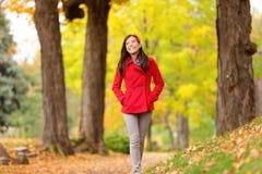 Fallmädchen, das auf den Herbstwaldweg glücklich geht Stockfotografie