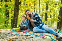 fallna leaves Skäggig farsa för Hipster med den gulliga sonen att spendera tid tillsammans i skogfamiljtid Familjfritid _ royaltyfria bilder