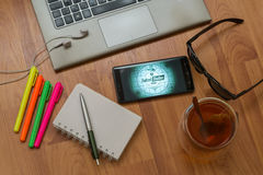 Fallout Shelter. Nitra, Slovakia, april 3, 2017: Fallout Shelter application in a mobile phone screen. Workplace with a laptop, an earphones, notepad, pen, tea Stock Images