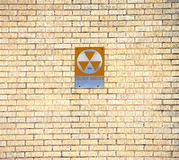 Fallout Shelter. An Old Fallout Shelter Sign Mounted On A yellow Brick Wall Royalty Free Stock Photo