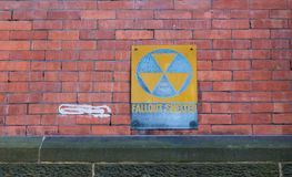 Fallout shelter sign on grungy faded wall. Old faded fallout shelter sign on grungy red brick wall background Stock Image