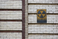 Fallout shelter sign. Old cold war fallout shelter sign on brick wall Stock Photos