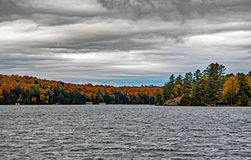 Falls Colors And Ominous Clouds On Lake Rosseau. Fall colours signify the end of the vacation season in the Muskoka cottage country of Ontario, Canada. The scene stock photos