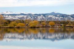 Falls Reflection on Lake. Fall colors against the snow capped mountains and reflection of both in the lake in the foreground.  Focus is on horizon line Stock Photo