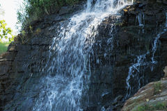 Falls. The water stream falls from a high rock Royalty Free Stock Photos