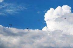 Fallschirmspringer fliegen in den bewölkten Himmel Lizenzfreie Stockfotos