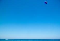 Fallschirmspringer im blauen Himmel über dem blauen Meer Lizenzfreie Stockfotografie