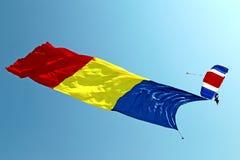 Fallschirmspringer mit der rumänischen Flagge im Himmel Lizenzfreies Stockfoto