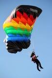 Fallskärmshopparen med färgrikt hoppa fallskärm arkivbild