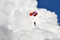 Fallskärmsjägarenedstigning med fluffig vit molnbakgrund royaltyfri foto