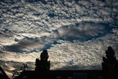 A fallstreak hole, also known as a punch hole cloud or cloud hole, appearing in altocumulus clouds stock image