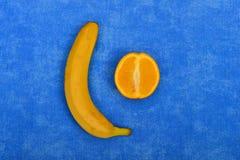Fallus i testicles na tle, bananie i pomarańczach z kondomem błękitnych, obrazy stock
