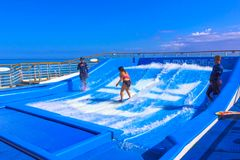 Falmouth, Jamaica - May 02, 2018: Woman surfing on the FlowRider aboard the Oasis of the Seas by Royal Caribbean. Falmouth, Jamaica - May 02, 2018: Woman surfing Royalty Free Stock Photo