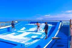 Falmouth, Jamaica - May 02, 2018: Woman surfing on the FlowRider aboard the Oasis of the Seas by Royal Caribbean. Falmouth, Jamaica - May 02, 2018: Woman surfing Stock Images
