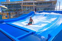 Falmouth, Jamaica - May 02, 2018: Woman surfing on the FlowRider aboard the Oasis of the Seas by Royal Caribbean. Falmouth, Jamaica - May 02, 2018: Woman surfing Royalty Free Stock Photos