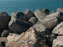 Falochron robić głazy, skały i moulded beton z błękitną ocean wodą w tle, fotografia royalty free
