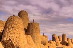 Falochrony przeciw chmurnemu niebu Fotografia Stock