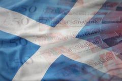 falowanie flaga państowowa Scotland na funta pieniądze banknotów tle pojęcia tła diety jaj złoty finansów Fotografia Stock