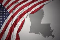 Falowanie flaga państowowa zlani stany America na szarości Louisiana stanu mapy tle fotografia royalty free