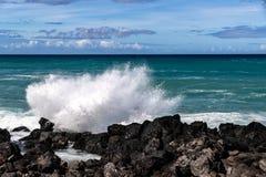 Falowy łamanie na czarnej lawy skale w Hawaje Biała kiść w powietrzu Ocean, niebieskie niebo i chmury w tle, obrazy royalty free