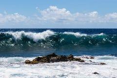 Falowy łamanie na morzu w Hawaje; powulkaniczna skała i piana w przedpolu Błękitny ocean, niebo, chmurnieje w tle obraz stock