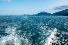 Falowy ślad z biel pianą na wody morskiej powierzchni behind szybki poruszający motorboat lub jacht Małe wyspy na horyzont linii Obraz Stock