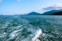 Falowy ślad z biel pianą na wody morskiej powierzchni behind szybki poruszający motorboat lub jacht Małe wyspy na horyzont linii Obrazy Royalty Free