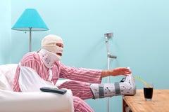 Falsch verletzter Mann, der zu Hause wieder herstellt Stockbilder