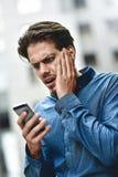 Falsche Nachrichten Geschäftsmann wurde die Nachrichten schlecht telefonisch, die an der Straße stehen Lizenzfreie Stockfotografie